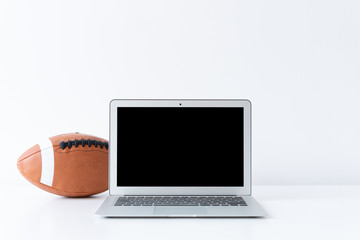 Open laptop with football or rugby ball on the desk with white background