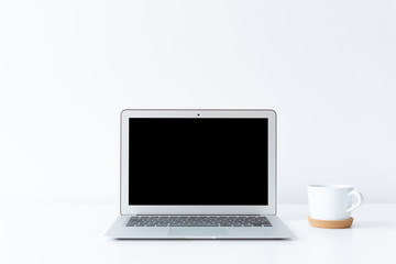 Open laptop and cup of coffee or tea on the desk with white background