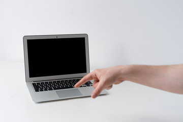 Open laptop with finger pointing on the desk with white background