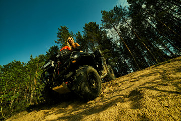 Poster Motorise Beautiful blonde girl on a black ATV rides on the river, standing on the mountain. Around the forest, sand and blue sky.She rides on a green swamp, in the mud and all wet. She's wearing a blue bikini.