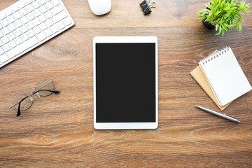 Wall Mural - White tablet with black blank screen is on top of wood desk table with blank notebook and supplies. Top view, flat lay.