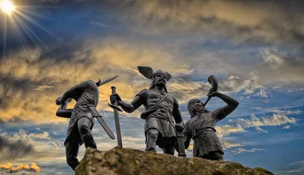 Old Norse God Odin on a rock, flanked by two Vikings (toy soldiers), one of them raised a sword and the other is trumpeting with horn, blue sky, bright sun, dramatic clouds