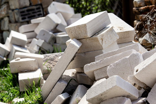 A pile of construction waste is in the yard. White brick or foam block
