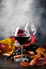 Red wine in wine glass, autumn still life with red and yellow leaves, wine tasting, copy space, selective focus