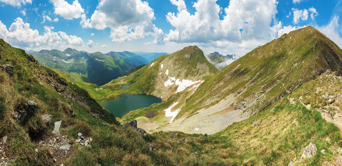 panorama of fagaras mountain in summer. glacier lake capra between hills. beautiful landscape with steep slopes, grassy meadows and peak. wonderful weather with gorgeous cloudscape on the blue sky