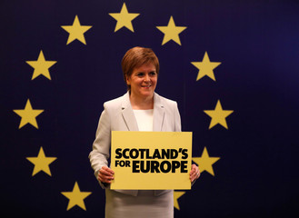 Scotland's First Minister Nicola Sturgeon stands in front of a European Union flag at the Scottish National Party (SNP) conference in Edinburgh