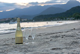 bottle of sparkling wine with two bowls crossed on the sand