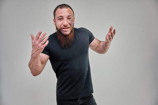Young brutal man with a beard, bodybuilder in a black t-shirt is standing, posing, talking on a white background with emotions. Beautiful male body. Concept art.