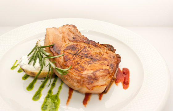 juicy piece of pork chop with potatoes, stuffed with cream sauce, rosemary, and kiwi sauce.on a white plate, a general view from above