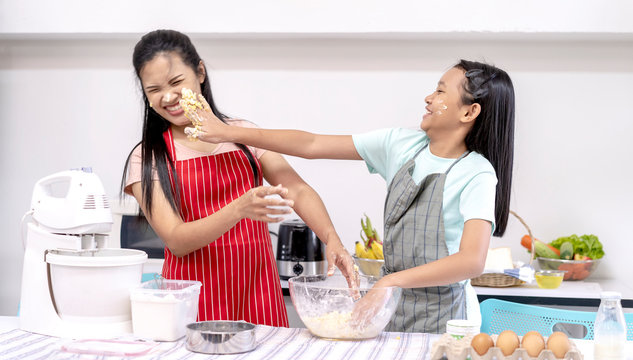 Asian family cooking food in kitchen. Happy teenage girl with her mother mixing batter in the bowl together and joyful. good team,Time of happiness. vacation holiday and Cooking together concept
