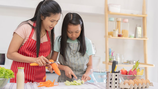 Asian family cooking food in kitchen while young girl in apron cooking, cutting, slicing cucumber for salad. good team,Time of happiness. vacation holiday and Cooking together concept