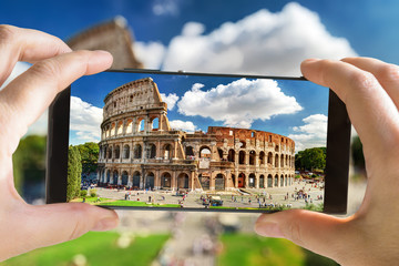 Tourist taking photo of the Ancient Roman Colosseum, Rome, Italy