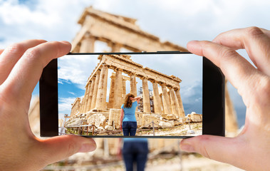 Fototapete - Tourist taking photo of young woman in Athens by cell phone, Greece