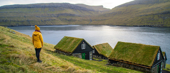 Tourist woman wearing yellow rain coat overlooking traditional Scandinavian village houses with green grass roof. Beautiful tourist spot/attraction located at Vágar Island, Faroe Islands, Denmark.