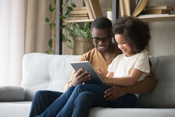 African father holds on lap daughter having fun use tablet