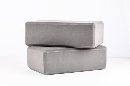 Two gray blocks for yoga on a white