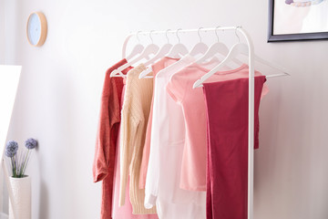 Rack with stylish female clothes in dressing room