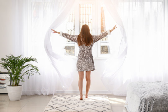 Young woman opening light curtains in bedroom at home