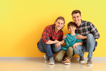Happy gay couple with adopted child near color wall
