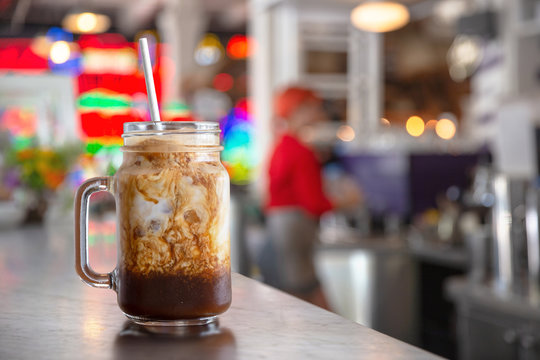 Freshly served iced latte coffee drink in a jar, on cafe diner counter, with mocha syrup cream swirl