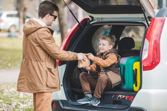father with son packing bags to car trunk. car travel concept