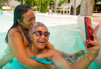 lifestyle outdoors portrait of Asian girlfriends enjoying Summer holidays at tropical beach resort swimming pool taking selfie photo with mobile phone playing