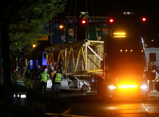 Part of a construction crane that fell in a deadly accident is removed from the scene on Mercer Street in Seattle