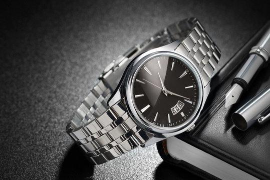 Steel wristwatch on black background
