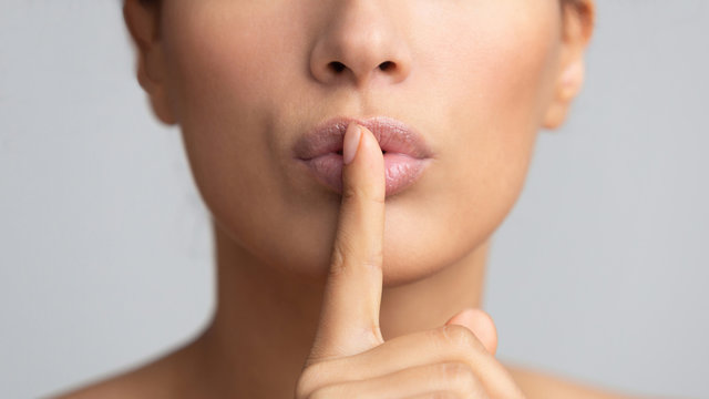 Women's secret. Woman holding finger on lips