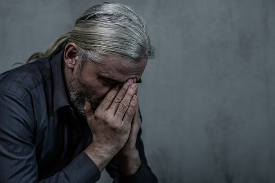 Senior man covering face and crying on dark background. Empty space for text