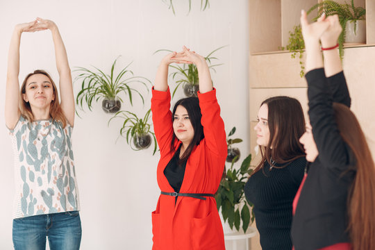 Team women doing exercises in office. Exercising females at work. Benefits of fitness stretching for employees and managers.