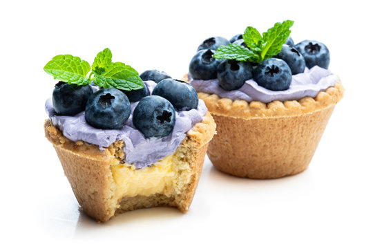 Mini tarts with blue cream and fresh blueberries isolated on white background