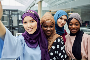 Group of four Asian and African Muslim women in fashionable traditional clothes taking selfie in shopping mall. Focus on white skinned asian beautiful girl in blue dress.
