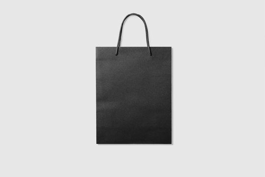 Mockup of a blank black paper shopping bag with handles on light grey background. High resolution.