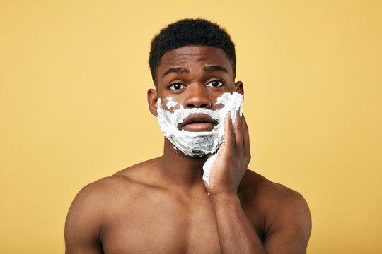grooming concept. Puzzled African man going to shave beard, poses half naked,daily routine. pastime