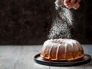 Woman's hand sprinkling icing sugar over fresh muffin cake. Powder sugar falls on fresh perfect muffin cake. Copy space for text. Ideas and recipes for breakfast or dessert Wall mural