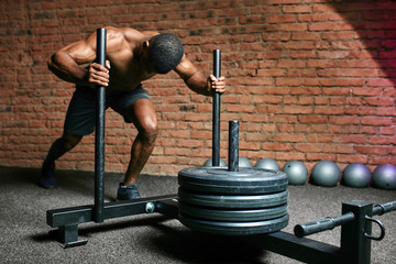 African athletic sportsman pushing sled in cross training gym. Muscular and strong man pushing the sled cross fit equipment on artificial grass turf.