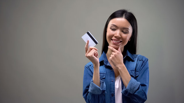 Smiling asian woman holding credit card and thinking about shopping, no limits