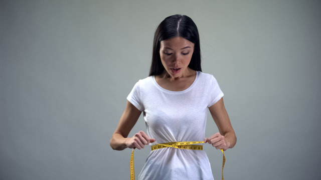 Asian woman measuring waist with tape, desire to lose weight, anorexia risk