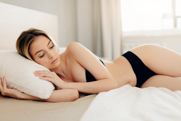 Blonde woman in black underwear sleeping in bed in seductive pose without blanket, her head resting on a pillow with her hands beside her head.