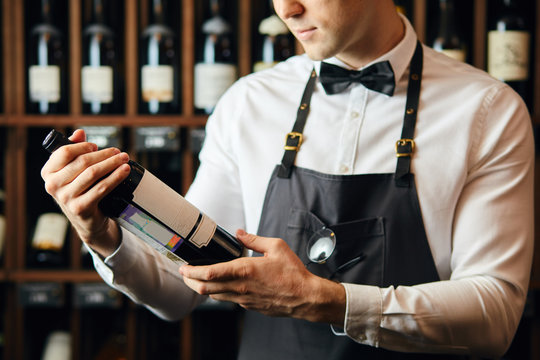 Cropped shot of young caucasian cavist dressed in white shirt and bowtie working in big vine shop presenting a bottle of red wine to customer
