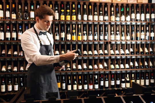 Caucasian male cavist in white shirt, grey apron and bow tie holding wine bottle against the sale shelves of a wine store or restaurant in natural light