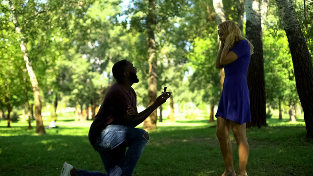 Surprise engagement in park, kneeling man makes proposal with ring, happy couple