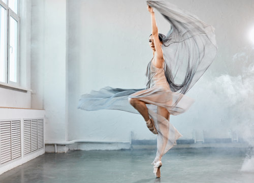 Full size portrait of talanted ballet student woman wears grey fluttering scenic dress giving a performance on a final exam in light studio on white smoky background.