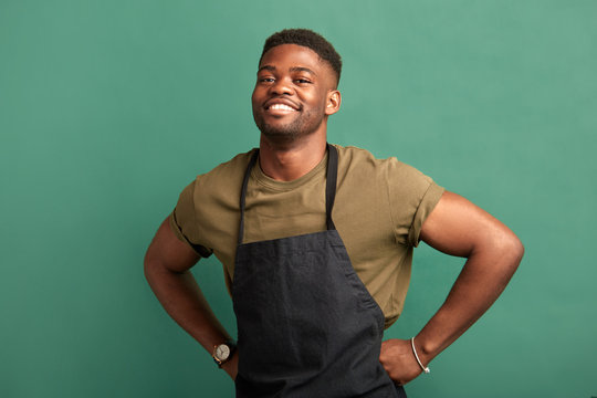African male farmer with muscular hands and sportive body, dressed in apron smiling at camera with toothy smile over green background