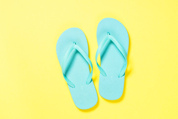 Blue flip flops on yellow background.