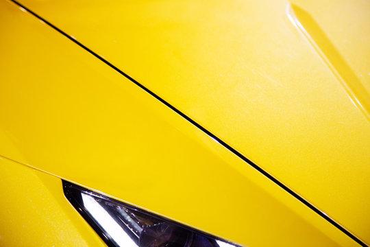 Car headlights of yellow sport car. Exterior detail