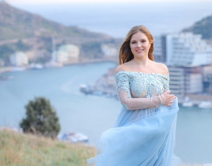 A girl with long hair on the beach. She's wearing a beautiful blue dress .    In the background view of the Bay, sea and city. Soft focus.