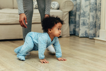 Side view of cute baby boy crawling on floor at home Wall mural