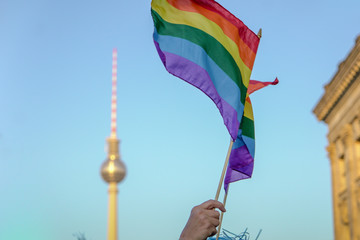 LOW ANGLE VIEW OF HAND HOLDING RAINBOW FLAG DURING CSD-PARADE IN BERLIN